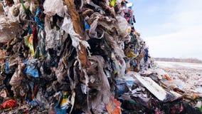Plast- packar, polyetylen i en avskrädeförrådsplats Stora högar av avskräde Dockaskott arkivfilmer