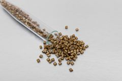 Plast- paletter Plast- råvaror i partiklar för bransch Polymeric färgguld på en silverbakgrund Plast- partiklar after Royaltyfria Bilder