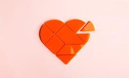 Plast- pussel i form av hjärta med det disconnected stycket på en rosa bakgrund arkivfoto