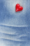 Plast- röd hjärta på jeanstextur Royaltyfri Bild