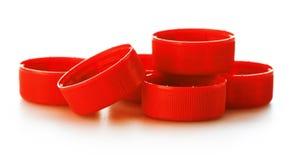 Plast- röda kapsyler på vit Arkivbilder