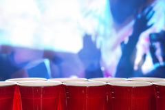 Plast- röda partikoppar i rad i en nattklubb mycket av folk som dansar på dansgolvet i bakgrunden royaltyfri foto