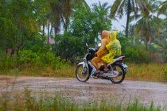 Plast- regnrockar, medan rida en sparkcykel i Cambodja Arkivbild