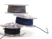 Plast- rulle tre av trådar för symaskin på en vitbac Arkivbild