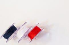 Plast- rulle tre av trådar, för symaskin på vita lodisar royaltyfri bild