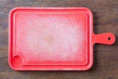 Plast- skärbräda på en gammal lantlig trätabell royaltyfri fotografi