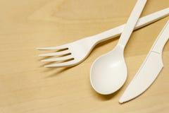 Plast- sked och gaffel på en trätabell royaltyfri bild