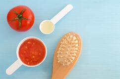 Plast- skopor med den tomatpuré-, olivolja- och wooderhårborsten Ingredienser för att förbereda den hemlagade hårmaskeringen Diy  royaltyfria bilder