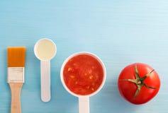 Plast- skopor med tomatpuré och olivolja Ingredienser för att förbereda den hemlagade ansikts- maskeringen Diy skönhetsmedelrecep royaltyfri foto
