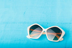Plast- solglasögon på blått Arkivbilder