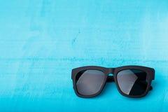 Plast- solglasögon på blått Arkivfoto
