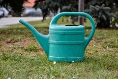 Plast- som bevattnar kan i gräs i trädgården Royaltyfri Fotografi