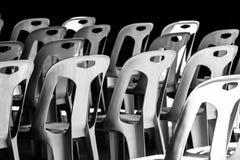 Plast- stol som staplas i solen och i skuggan arkivbild