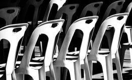 Plast- stol som staplas i solen och i skuggan royaltyfri fotografi