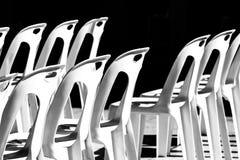 Plast- stol som staplas i solen och i skuggan royaltyfria bilder
