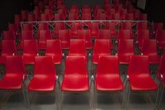 Plast- stolar av rött Fotografering för Bildbyråer