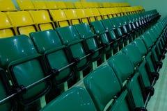 Plast- stolar för åskådare i idrottshallen Salong med rader av lyftta gröna och gula platser arkivfoto