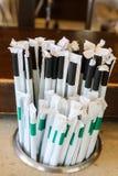 Plast- sugrör med pappers- omslag i räknarehållare - sugrören, som många tillstånd och länder kriminaliserar men, används fortfar royaltyfri bild