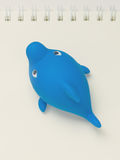 Plast- sväva Toy Shark på en anteckningsbok Hand-drog konturlinjer och slaglängder Royaltyfria Foton