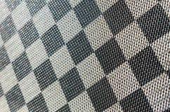 Plast- textur i form av ett mycket litet torkdukeband som målas i svart och grå färger i stilen av en schackbräde Skjuten makro arkivbilder