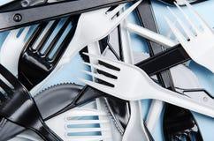 Plast- vita och svarta gafflar och knivar p? en bl? bakgrund Plast- disk f?r begrepp, plast- f?rorening Lekmanna- l?genhet, ?verk arkivfoto