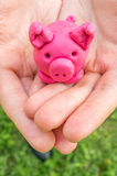 Plasteline piggy ως moneybox στα χέρια Στοκ φωτογραφία με δικαίωμα ελεύθερης χρήσης