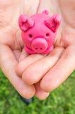 Plasteline som är piggy som moneybox i händer Royaltyfri Fotografi