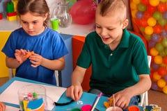 Plastellina som modellerar lera i barngrupp i skola Arkivfoton