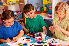 Plastellina som modellerar lera i barngrupp Läraren undervisar i skola Arkivfoto