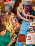 Plastellina som modellerar lera i barngrupp Läraren undervisar i skola Arkivbild