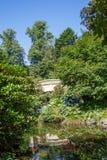 Plaster Bridge Through Trees in Garden Stock Images