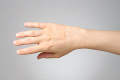 Plaster on female hand stock images