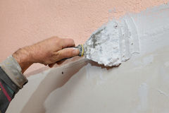 Plaster and gypsum. Worker spreading plaster with trowel to gypsum board and fiber mesh Royalty Free Stock Image