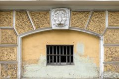 Plaster head of a lion on the facade above a window with a lattice Royalty Free Stock Photo