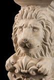 Plaster lion sculpture, pommel column. On a black background stock photos