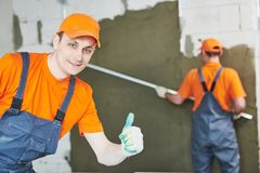 Plaster service. portrait of male plasterer. In front of plastering work Stock Photo