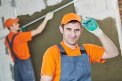 Plaster service. portrait of male plasterer. In front of plastering work Stock Image
