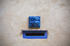 Plaster wall with blue decorative letter slot mailbox Royalty Free Stock Photo