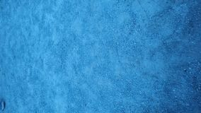 Plaster wall painted in light blue paint. Close-up stock photography