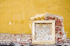 Plaster wall and wood frame. Side of wall with yellow plaster falling off brick wall and wood frame Stock Image