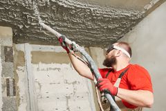 Plasterer spraying plastering mortar on ceiling with sprayer machine royalty free stock photo