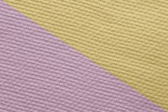 Plastered textured with small squares wall painted diagonally. In two colors purple and yellow Royalty Free Stock Photo