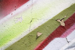 Plastered wall with peeling graffiti. Close-up view of a colorful peeling graffiti on a plastered wall stock photos