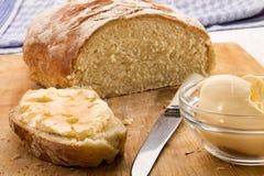 Plasterek świeżo piec floured kraju chleb z masłem Obrazy Royalty Free