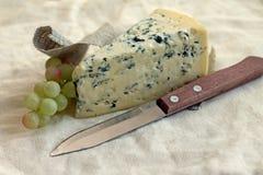 Plasterek błękitny ser z nożem i winogronami Fotografia Stock