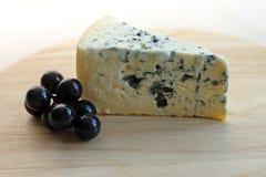 Plasterek błękitny ser z winogronami na drewnianym tle Obrazy Royalty Free