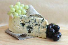 Plasterek błękitny ser z winogronami na drewnianym tle Zdjęcia Royalty Free