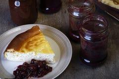 Plasterek cheesecake na talerzu z dżemem Zdjęcia Stock