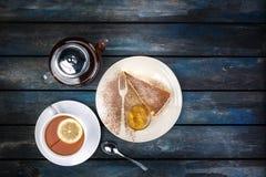 Plasterek Cheesecake z dżemem i herbacianym czajnikiem z cytryną na barwionym drewnianym tle Odgórny widok zdjęcia stock