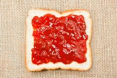 Plasterek chleb z truskawkowym dżemem na grabije tle Zdjęcie Stock